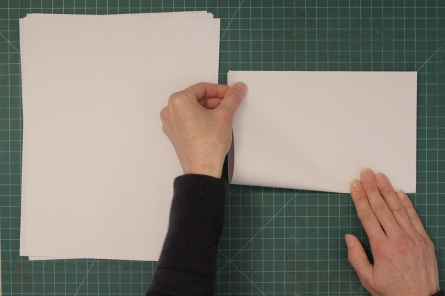 Folding blank sheets of paper in half