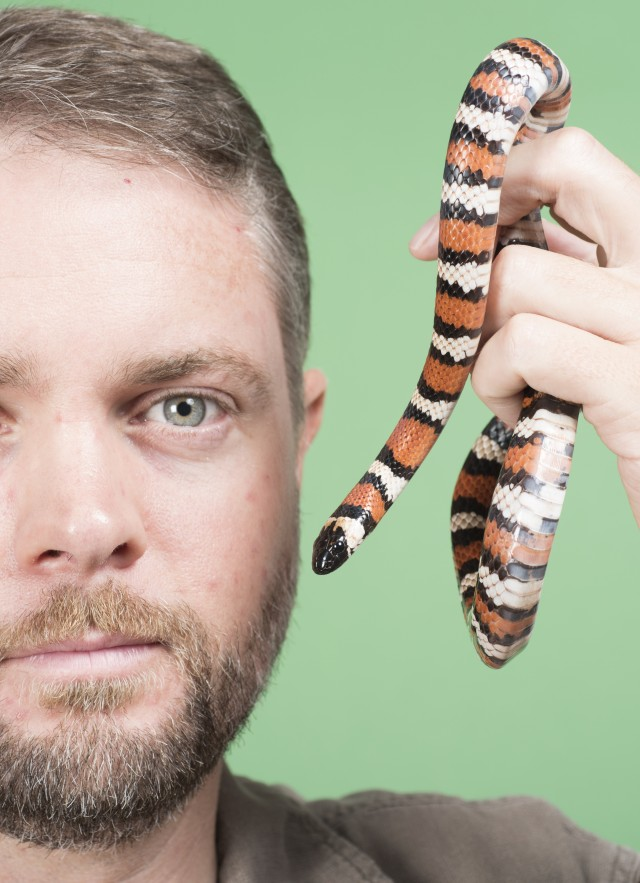 Dr. Greg Pauly with a snake in front of a green screen.
