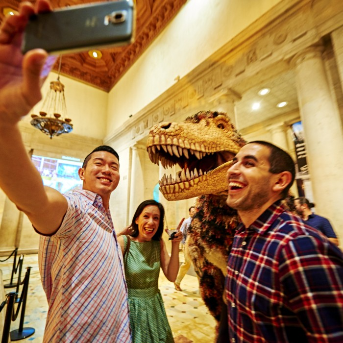guests taking selfie with dinosaur encounters puppet grand foyer