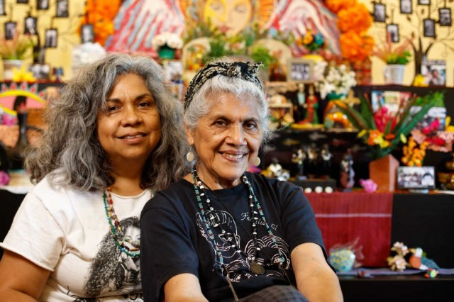 Ofrenda artists pictured in front of altar