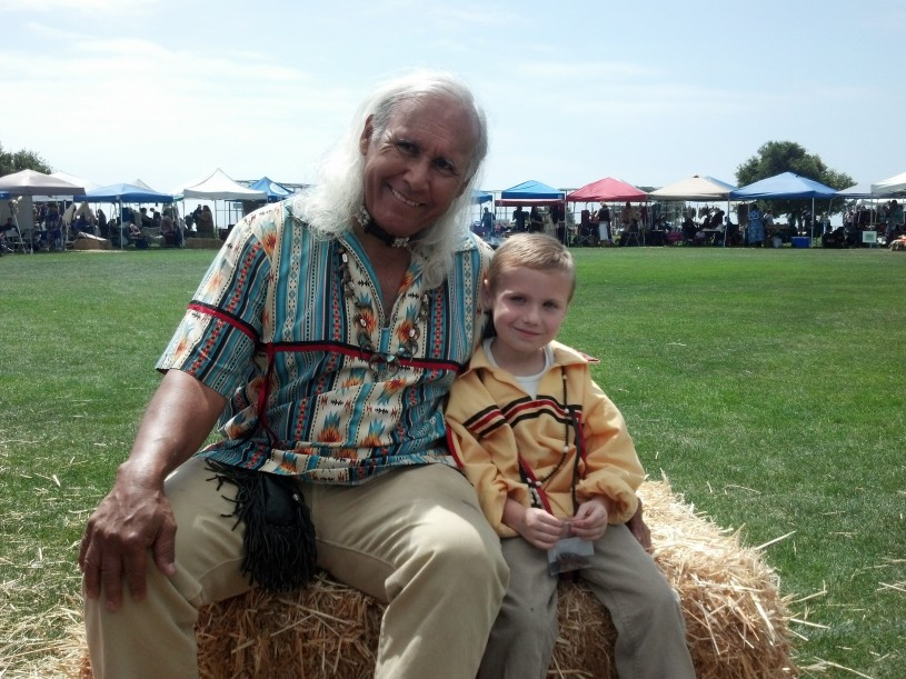 Alan sits next to his grandson Caden at the Chumash Powwow in Malibu California