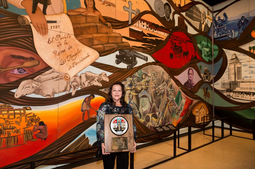 Artist Barbara Carrasco in front of L.A. History: A Mexican Perspective with a commendation from Los Angeles County
