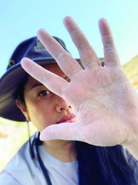 Close up of diana kou's dusty hand with her face out of focus
